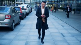 Commerciële cluster met een bureaumanager met een smartphone die een wandeling langs het hebben Rood episch draak6k schot stock footage