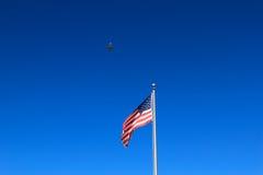 Commerciële jet die in de hemel over de Amerikaanse vlag vliegen Stock Foto