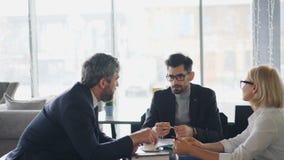 Commerciële team midden oude mannen en hogere vrouw die in koffie over koffie spreken stock videobeelden