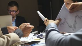 Commerciële team planningsstrategie voor collectief project in bureau Jonge medewerkers die bij lijst en het onderzoeken zitten stock footage