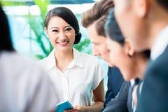 Commerciële teamvergadering van Aziatische en Kaukasische stafmedewerkers Stock Afbeeldingen