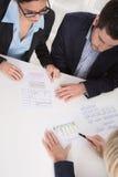 Commerciële vergadering Drie mensen die bij de lijst in een bureau zitten stock fotografie