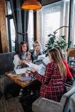 Commerciële vergadering in een koffie, vier jonge vrouwen die bij een lijst zitten en documenten bespreken royalty-vrije stock foto