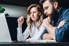 Commerciële vergadering groepswerk Onderneemster en zakenmanzitting bij lijst voor laptop en het werken stock afbeeldingen
