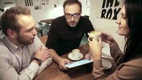 Commerciële vergadering in koffie het team gebruikt de tablet stock footage