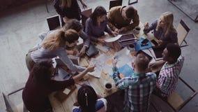 Commerciële vergadering op modern kantoor Hoogste mening van multiraciale groep mensen die dichtbij de lijst samenwerken Langzame stock video