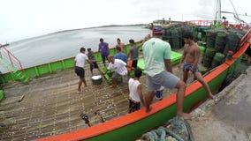 Commerciële vissers die vangstvissen van schip koude opslag aan boord vervoeren stock footage