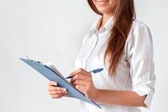 Commerci?le vergadering Vrouw status geïsoleerd op wit met klembord die nota's over document gelukkig close-up nemen stock foto