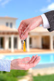 Commercial agent giving keys to customer vertical composition. Arm of a commercial agent giving some keys to building a home buyer with home background, vertical stock image