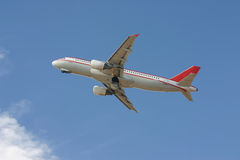 Commercial aircraft. Red and white commercial aircraft taking off Stock Image