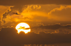 Commercial Aircraft On Approach Above Large Summer. This commercial aircraft leaves a backlit vapor trail as it passess near a large, hot summer sunrise stock photos