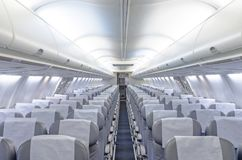 Commercial aircraft cabin with rows of seats down the aisle. Commercial aircraft cabin with rows of seats down the aisle Royalty Free Stock Photography