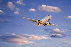 Commercial Aircraft in Evening Sky Stock Photo