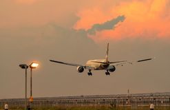 Commercial airline. Passenger plane landing at airport with beautiful sunset sky and clouds. Arrival flight. Airplane flying. Over runway. Fence and taxiway stock photography