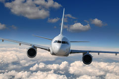 Commercial airliner in flight. With clouds on the background Royalty Free Stock Images
