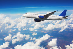 Commercial airliner flying above clouds Stock Image