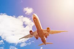 Commercial airliner flying near clouds with blue sky and sun flare. Travel or business trip concept image. Toned. Commercial airliner flying near clouds with royalty free stock image