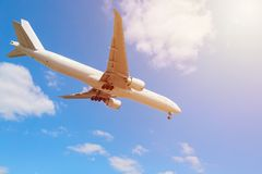 Commercial airliner flying near clouds and landing with blue sky and sun flare. Travel or business trip concept image. Toned. Commercial airliner flying near stock photo