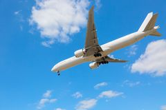 Commercial airliner flying near clouds and landing with blue sky. Travel or business trip concept image. Commercial airliner flying near clouds and landing with stock photo