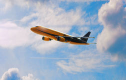 Commercial Airplane in Flight Behind Blue Skies Stock Photography