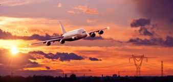 Commercial airplane flying above city in sunset ligt Stock Photo
