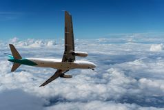 Commercial airplane flying above clouds and clear blue sky over. Beautiful scenery nature background,concept business travel and transportation background Stock Photos