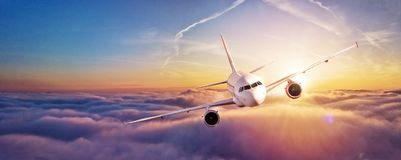 Commercial airplane flying above clouds. In dramatic sunset light. High resolution of image. Fast Travel and transportation concept Stock Images