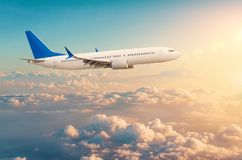 Commercial airplane flying above cloudscape in dramatic toned sunset light stock photo