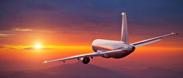 Commercial airplane flying above mountains in sunset Royalty Free Stock Images