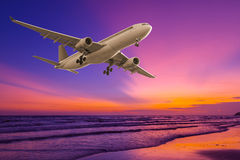 Commercial airplane flying above the sea at sunset Stock Image