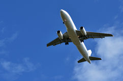 Commercial airplane flying in blue sky Stock Photos