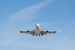 Commercial airplane flying in blue sky, full flap and landing ge Stock Photo