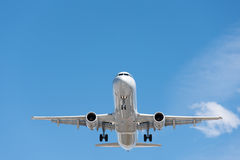 Commercial airplane flying in blue sky, full flap and landing ge Royalty Free Stock Image
