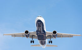 Commercial airplane flying in blue sky, full flap and landing ge Royalty Free Stock Photo