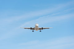 Commercial airplane flying in blue sky, full flap and landing ge Stock Photography