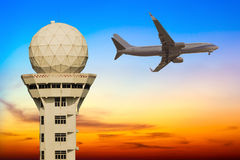 Commercial airplane flying over airport control tower Royalty Free Stock Photography
