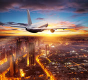 Commercial airplane flying over Dubai city Stock Images