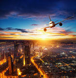 Commercial airplane flying over modern city Stock Photos