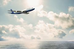 Commercial airplane flying over water. E view of commercial jumbo airbus flying over water. Blue and white airplane with copy space against cloud background Stock Photography