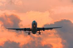 Commercial airplane flying runway airport above dramatic clouds. royalty free stock images