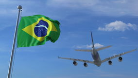 Commercial airplane landing behind waving Brazilian flag. Travel to Brazil conceptual 3D rendering. Commercial airplane landing behind waving flag Stock Photo