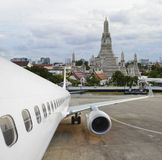 Commercial airplane parked at the airport with pagoda of Wat Arun in background.  stock image