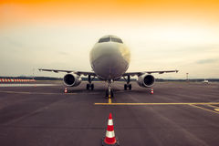 Commercial airplane parking at the airport, with traffic cone in Royalty Free Stock Images