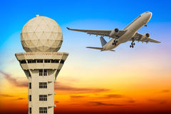 Commercial airplane take off over airport control tower at sunse Stock Images