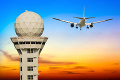Commercial airplane take off over airport control tower Stock Photography