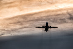 A commercial airplane during takeoff from the airport. Silhouette flying over sky at sunset or sunrise background, Stock Images