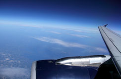 Commercial Airplane Wing in blue Sky. View from the inside of a flying commercial plane of its wing and jet engine against a blue sky and some land below Stock Photography
