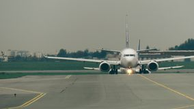 Commercial airplanes taxiing at international airport, front view Stock Photos