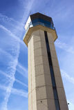 Commercial Airport Control Tower from close up perspective with sky criss-crossed by jet trails Royalty Free Stock Image