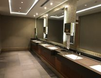 Commercial bathroom. Interiors shots of a modern bathroom. In the foreground the glass counter top washbasin and the big mirror royalty free stock photos